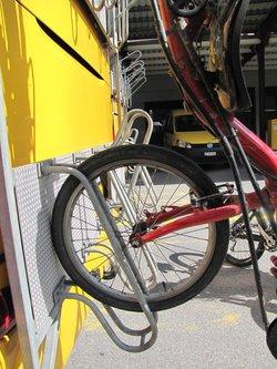 roue de vélo couché sur un porte vélo de car postal.jpg